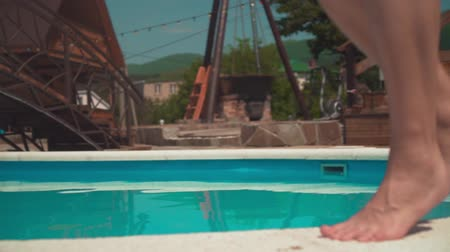 Close-up on a womans legs as she tiptoes along the edge of the pool, in slow motion. Wideo