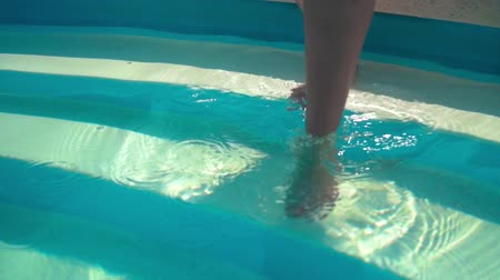 Close-up on a womans legs when she enters the pool, in slow motion.