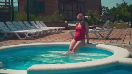 Beautiful pregnant girl in a red one-piece swimsuit and glasses sits near the pool with her legs down into the water.