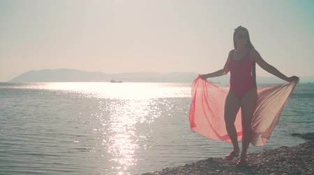 A pregnant girl in a red one-piece swimsuit walks along the seashore in the rays of the setting sun, holding a stole in her hands. Sun overexposure effect. Wideo