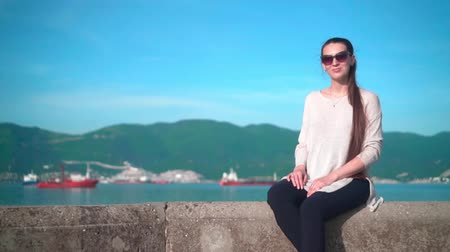 Young pregnant charming girl in sunglasses in clear weather in the summer. The girl sits on the embankment near the sea on the background of mountains and ships. Wideo