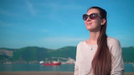 Young charming girl in sunglasses in clear summer weather. The girl sits on the embankment near the sea on the background of mountains and ships.
