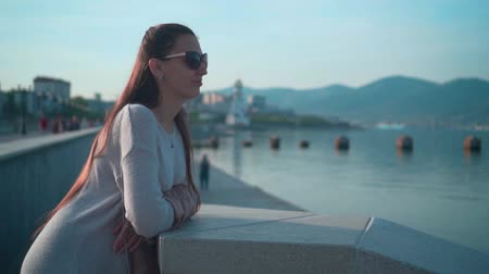 Young charming girl in sunglasses in clear summer weather. A girl stands on the embankment near the sea against the background of the port city.