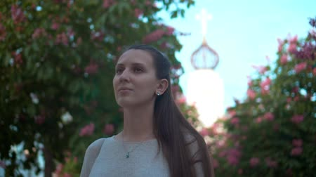 castanha : A young woman stands in a park of blooming pink chestnuts. Beautiful woman and blooming pink trees in the park against the backdrop of the church. Stock Footage
