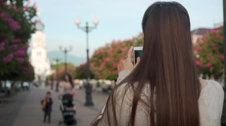 castanha : A young woman photographs on the phone in a park of blooming pink chestnuts. Woman backs into frame and blooming pink trees in the park against the background of the church. Stock Footage