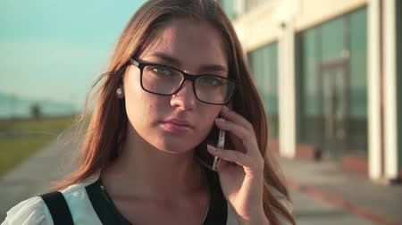 Caucasian young business woman in a white shirt and glasses walking on the street near a modern office building and talking on the phone. Close-up.