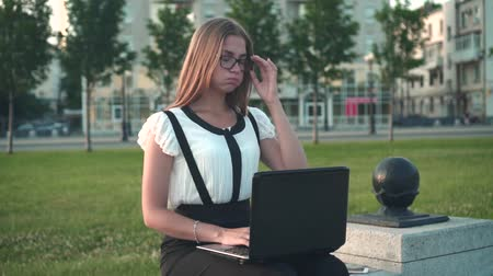 Caucasian young business woman in white shirt and glasses sits on a bench in the street and works behind a laptop. A close-up, the girl is tired, removes glasses from her eyes.