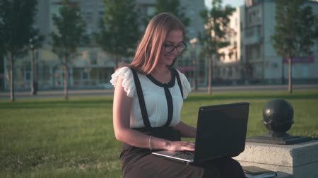 Caucasian young business woman in white shirt and glasses sits on a bench on the street and works on a laptop. The girl is satisfied with the work and smiles.