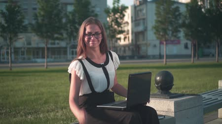 Caucasian young business woman in white shirt and glasses sits on a bench on the street and works on a laptop. The girl is not happy with the work and angry. Stock Footage