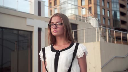 Caucasian young business woman in white shirt and glasses walking down the street near a modern office building. The average plan.