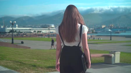 Caucasian young business woman in white shirt and glasses is walking, holding a laptop in hand, background of mountains and the sea. The camera moves behind the girl, the girl back in the frame. Stock mozgókép