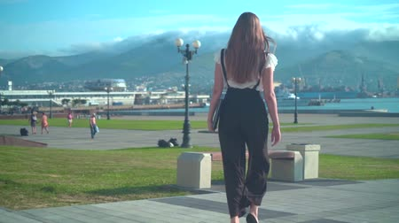 Caucasian young business woman in white shirt and glasses is walking, holding a laptop in hand, background of mountains and the sea. The camera moves behind the girl, the girl back in the frame. Wideo