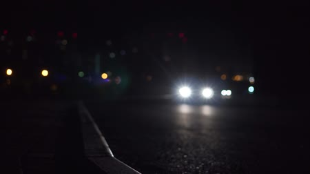 придорожный : City lights and cars driving in the background traffic. Night road, passing cars.