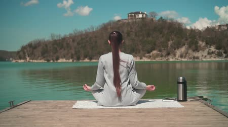 position du lotus : A young woman is meditating in the sun while sitting on a wooden pier of a lake on a spring day, relaxing in nature. Girl backs in the frame. Meditation harmony with nature.