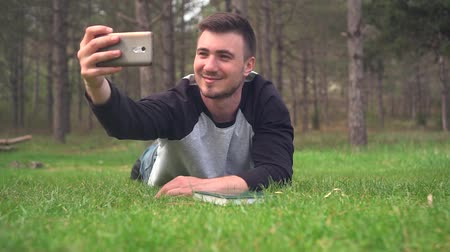читатель : A young guy lies on the green grass in the forest and takes a selfie on the phone. Rest, relaxation, pleasure. Background - pine forest. Стоковые видеозаписи