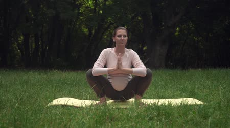 születés előtti : A pregnant woman practicing yoga in the park on a rug, doing the asana Malasana, a pose of a crow or a pose of a frog. Relaxation and being in asana.