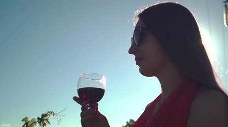 szőlőművelés : Girl in a red dress on a background of blue sky. A girl with long hair in glasses drinks red wine against a blue sky.