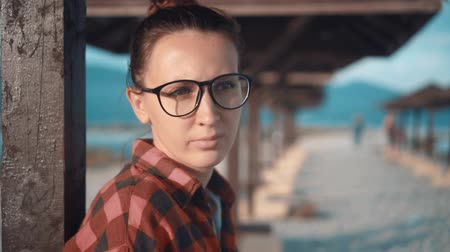 parasol : Beautiful young girl with glasses and a red checkered shirt in and relaxes. In the background are many wooden parasols on the beach. Stock Footage