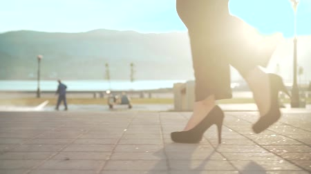 stepping : Female feet walking through the downtown. Businesswoman wearing shoes with heels. Stylish woman walking in city center.