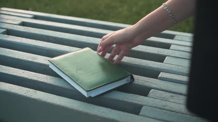 organizing : Close-up of a notebook lying on a bench. Female hand with a beautiful manicure takes a notebook.