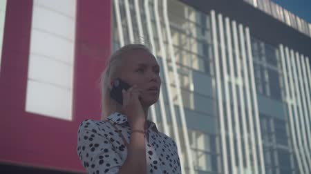 ortalama : Caucasian young business woman in a white shirt with black peas, standing on the street near the modern office building and talking on the phone. The average plan.