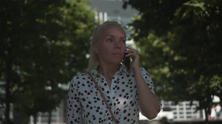 ortalama : Caucasian young business woman in a white shirt with black peas, walking down the street and talking on the phone against the background of an office building and green trees. The average plan.