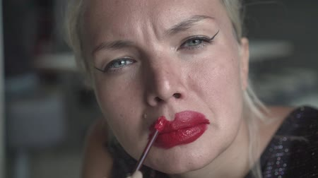 пятна : Close-up of a seductive blonde woman, carelessly putting on red lipstick. Makeup, sexy blonde unevenly puts red lipstick on her lips.