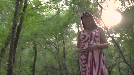 妊娠した : A pregnant girl is standing in the park. A girl with long dark hair in a striped white-red dress stands among the trees and holds her hand on her tummy.