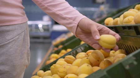решить : Girl in the supermarket chooses fruit, close-up. Female hand picks fruits in the supermarket.