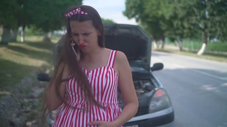 aflição : A pregnant young woman stands near a wrecked car on a rural road. Upset girl calls on the phone and asks for help, looking at the engine of the car. Stock Footage