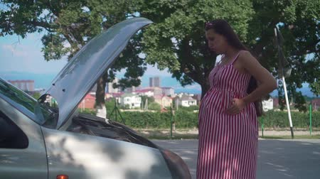 szál : A pregnant young woman stands near a wrecked car on a rural road. Upset girl does not know what to do with the breakdown, looking at the engine car.