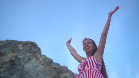 expectativa : Young pregnant charming girl in a striped red and white dress in clear summer weather. A girl stands at the foot of a rocky mountain and shows a sign of freedom, hands up.