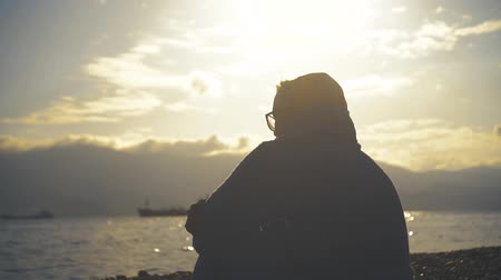 alpinista : Young attractive woman watching a sunset or sunrise on the beach against the background of the sea and mountains, a girl with glasses and a bathrobe sitting on the beach. Archivo de Video