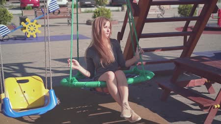szórakoztatás : Cute young girl walks in an urban environment. Happy girl in a gray dress swinging on a swing at the playground. Stock mozgókép