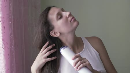 combing : The girl dries her hair with a hairdryer in the early morning. A young girl without makeup dries her hair with a hairdryer. Morning styling housewife. Stock Footage