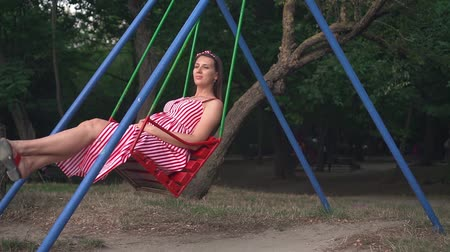 fertilidade : Pregnant girl in the park swinging on a swing. Happy girl with long dark hair in a striped white-red dress on a swing n the park.