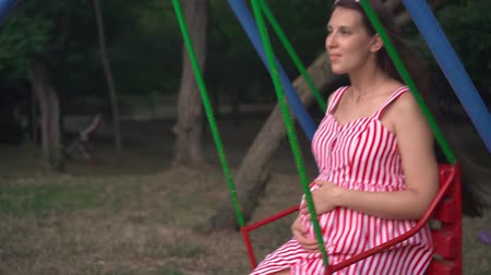 nascimento : Pregnant girl in the park swinging on a swing. Happy girl with long dark hair in a striped white-red dress on a swing n the park.