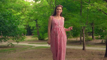 plodnost : A pregnant girl walks through the park. A girl with long dark hair in a striped white and red dress goes smiling and dancing among the trees.
