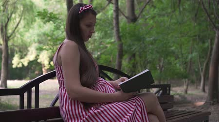 愛撫 : A pregnant girl is sitting on a bench in the park. A girl with long dark hair in a striped white-red dress enthusiastically reads a book on a bench.