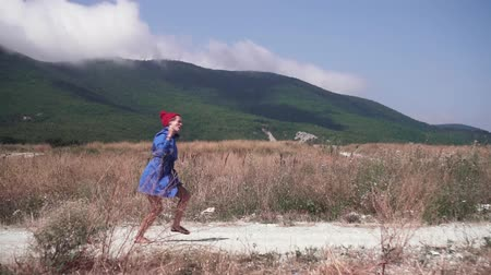 curtimento : Sexy girl running on a road in the mountains on a sunny summer day. The blonde has fun and running in a blue coat and red hat. Stock Footage