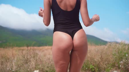 atleta : A hot woman in a black swimsuit is dancing. A woman with an attractive body shakes her ass. Beautiful girl passionately dancing in a black swimsuit moves her body. Vídeos