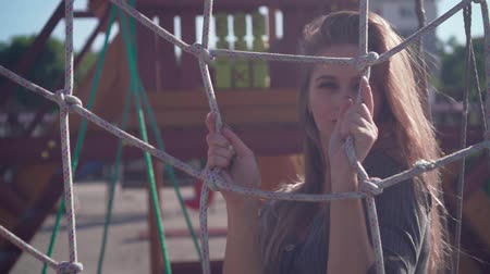 развлекательный : Cute young girl walks in an urban environment. Happy girl in a gray dress has fun, smiles at the playground, flirts playing with a rope net.