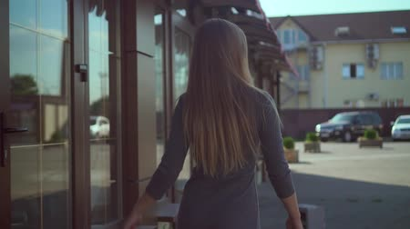 inspirar : Cute young girl walks in an urban environment. A happy girl in a gray dress has fun, smiles and flirts, the camera moves behind the girl. Stock Footage