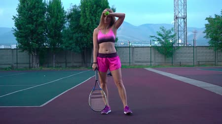 tennis stadium : Young pretty girl plays tennis. A blonde with long hair in a pink tracksuit professionally trains tennis. The girl serves the ball.