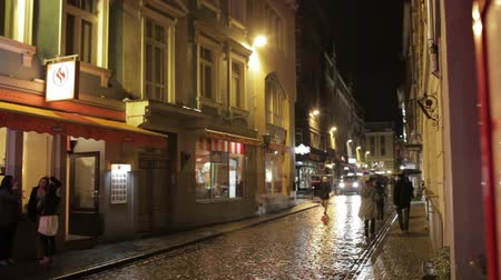 andar : People walking along street bars and restaurants in the evening in the old city of Riga after the rain.