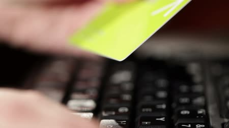 купить : Getting a credit card and typing. On-line shopping on the internet. Shallow depth of field. Warm light. Closeup.