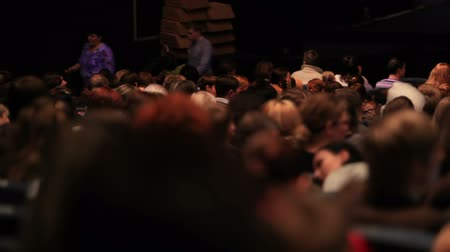blur : People in the theatre. Pan shot from the back.