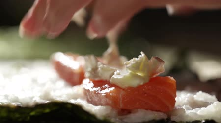 roll up : Making sushi rolls with salmon and philadelphia cheese.