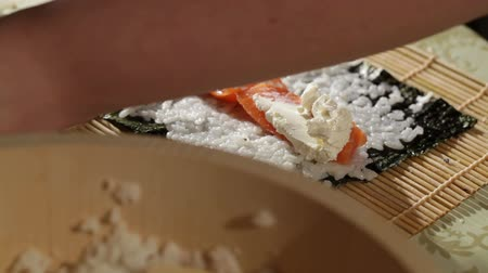 pieces of cheese : Making sushi rolls with salmon and philadelphia cheese.