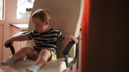 cadeira : Two year old boy is spinning on chair.